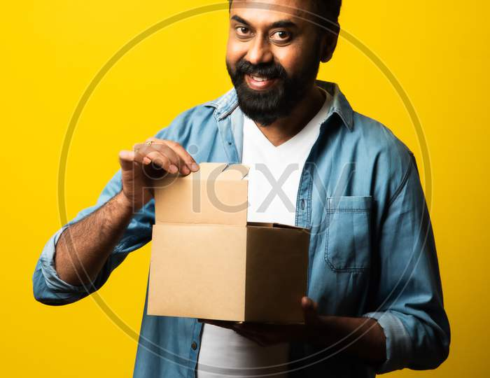 Indian Handsome Bearded Young Man Opening Box With Parcel While Standing Against Yellow Background