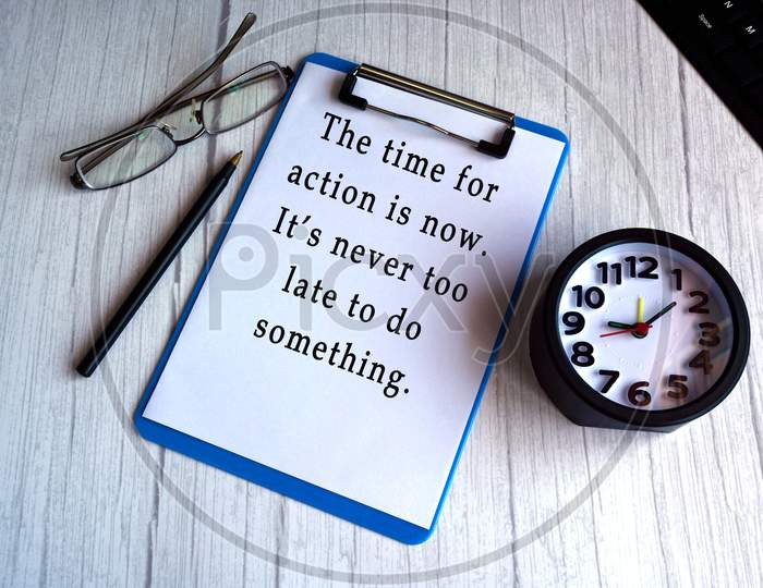Motivational And Inspirational Quote On Blue Clip Board With Alarm Clock, Glasses, Pen And Keyboard On Wooden Desk