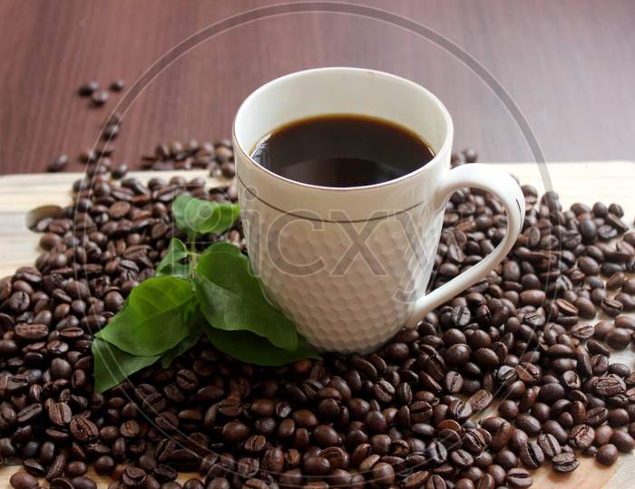 A Black Coffee In Beween Coffee Beans On A Table