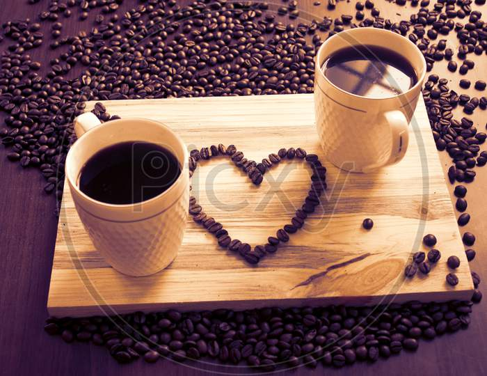 Two Coffee Cup And A Heart Sign With Beans