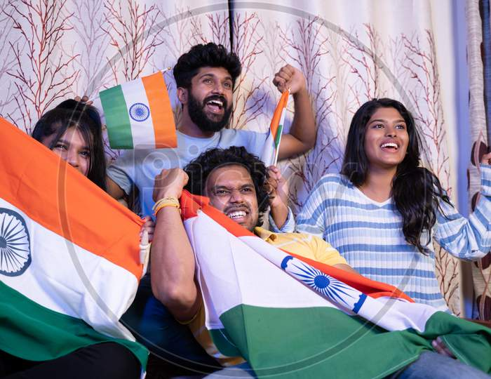 Group Of Friends Shouting India India While Watching Sports Match On Television At Home - Concept Of Group Of People Supporting Indian Cricket People