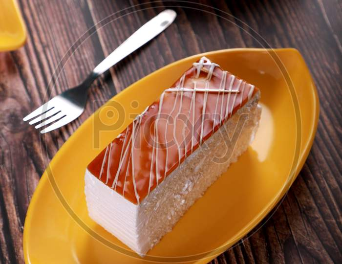 Caramel Pastry Cheese Cake On A Yellow Plate With Fork On Wooden Table