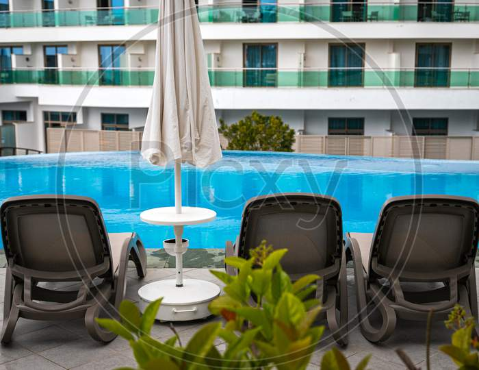 A  Comfortable Gray Sun Loungers Set Against The Backdrop Of A Beautiful Transparent Pool And Hotel. The Concept Of A Relaxing Seaside Vacation