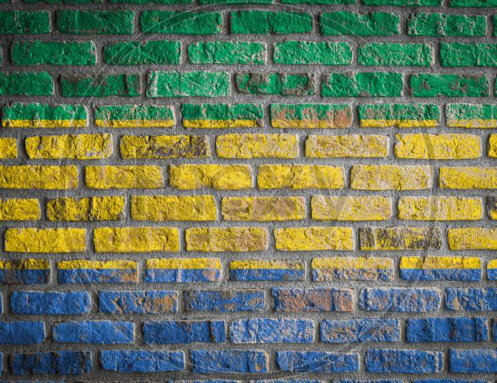 National Flag Of Gabon Depicting In Paint Colors On An Old Brick Wall. Flag  Banner On Brick Wall Background.
