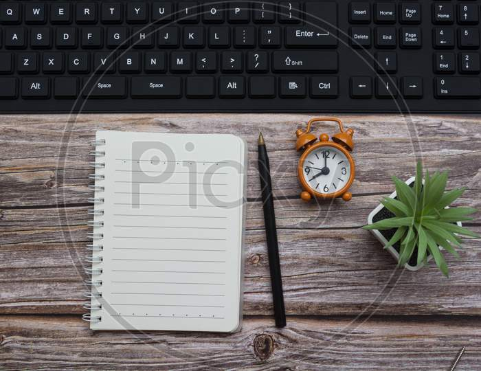 Notepad With Pen, Alarm Clock, Potted Plan And Keyboard On Wooden Desk
