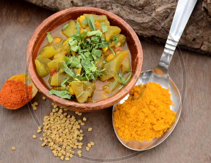 The Round Gourd Made Vegetable In The Wooden Bowl With Turmeric,Red Chilly Powder,And Greek, On The Brown Wooden Background.