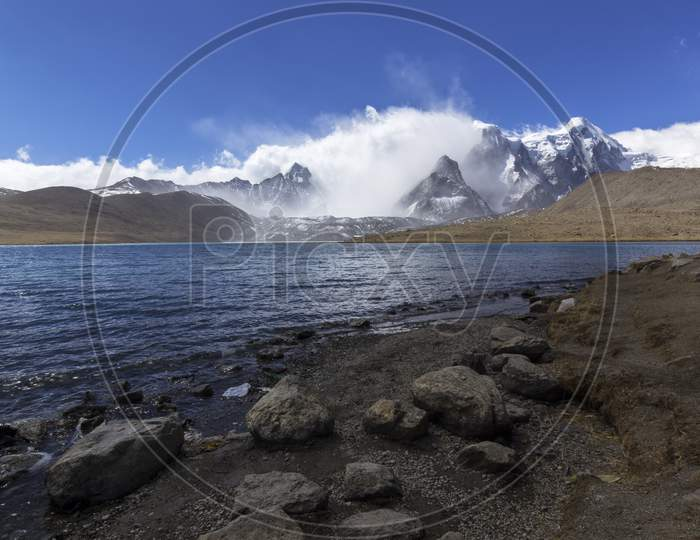A Beautiful Landscape Of Gurudongmar Lake With Rocks In Forte Ground And Mountain With Blue Sky In Background. Gurudongmar Lake One Of The Highest Lake Of The World And India Located At An Altitude Of 17,800 Ft, In The Indian State Of Sikkim