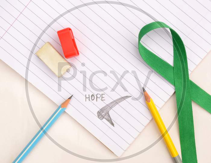 Pencil With Writing Hope Mental Health Awareness Concept Not Book ,Green Ribbon,Eraser,Sharpener On The White Background.