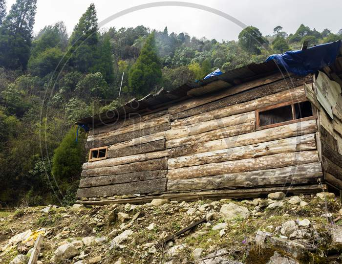 An Abandent Wooden House With Green Forest In Background At Lachung Village Of North Sikkim.