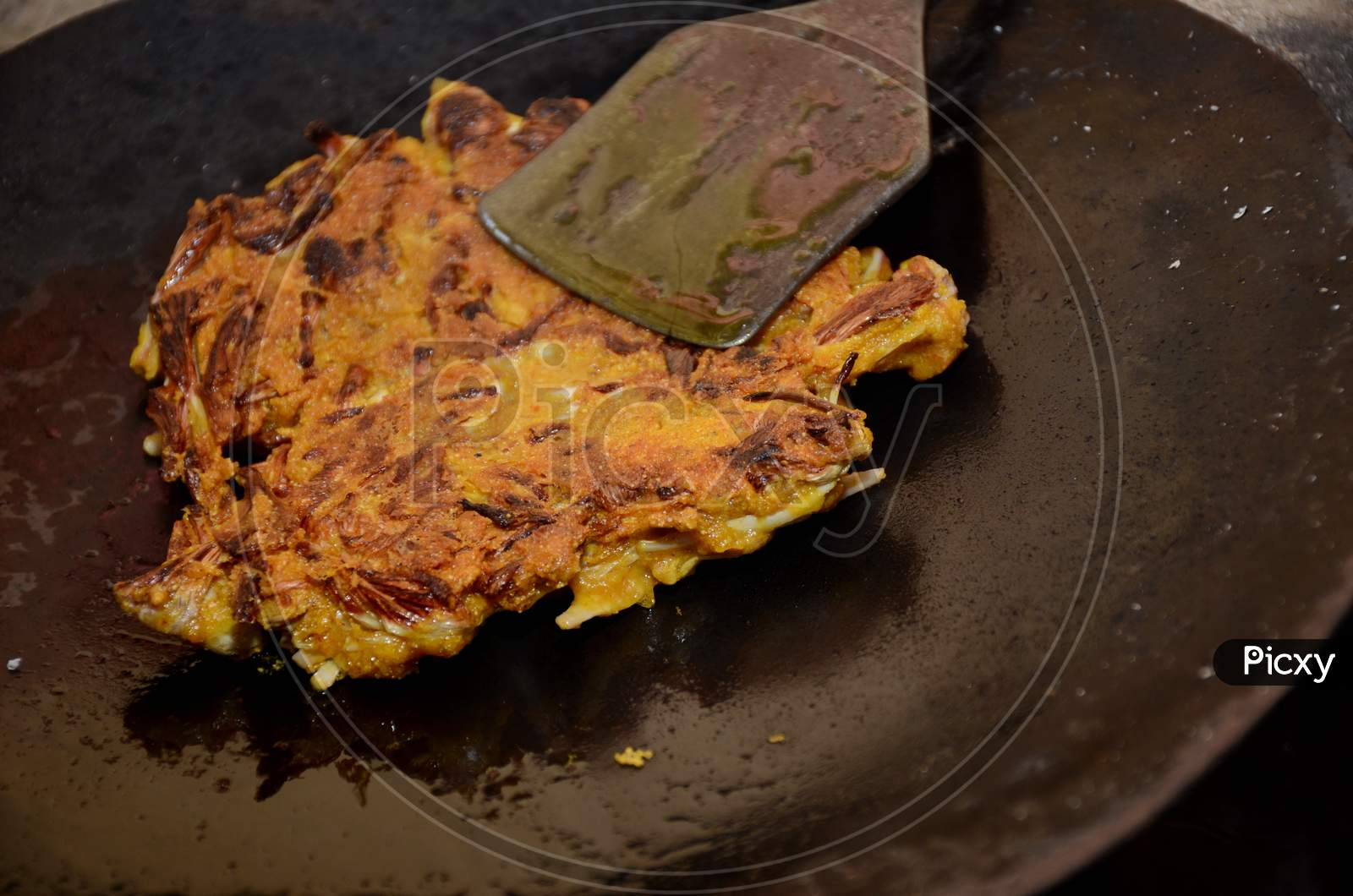 The Yellow Tree Flower Fried Made Veg With Metal Dark Vessel.