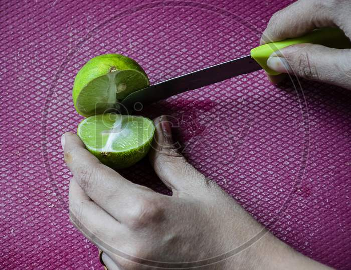 Stock Photo Of Women Cutting Fresh Juicy Lemon On Purple Color Chopping Board With Yellow Color Knife , Focus On Object. Blur Background.