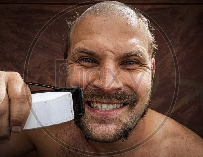 Adult Cheerful Man With A Beard Shaves His Beard At Home. The Guy Looks In The Bathroom Mirror And Uses The Electric Trimmer. Front View