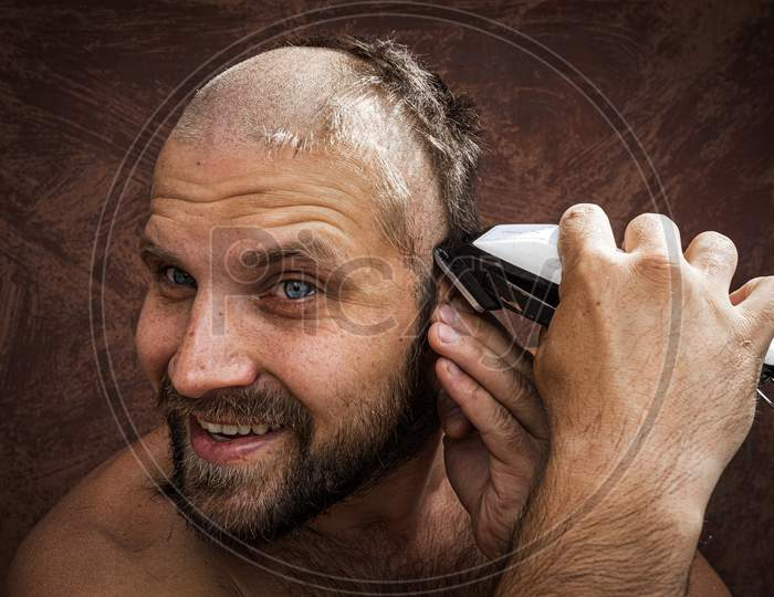 Caucasian Man Trying To Shave His Head With An Electric Razor. A Brutal Bald Man Holds A Razor In His Hand And Shaves Stubble On A Metal Background