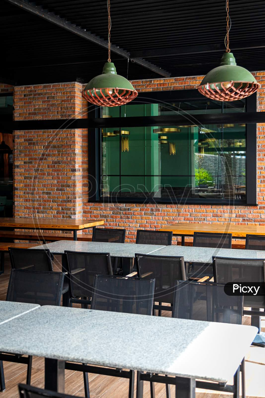 Huge Dining Area With Dark Tables And Chairs In A Loft-Style Street With Brick Walls And Metal Lamps