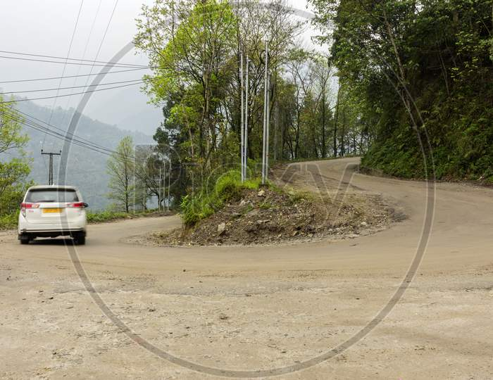 A Beautiful Landscape Of Dangerous Road Bend And A White Car In Motion Blur On The Way To North Sikkim, India.