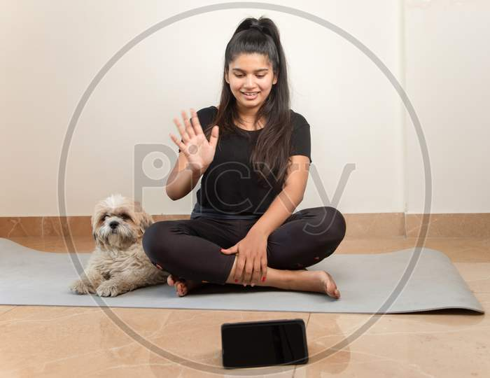Girl Greeting On Online Class From Mobile Phone For Exercise - Concept Of Online Yoga Live Streaming On A Smartphone - Yoga Trainer Teaching Via Internet From Home.