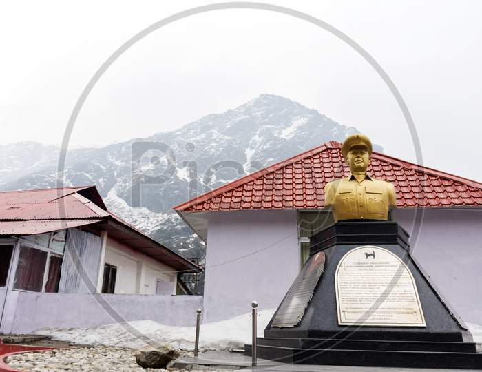 Statue Os A Soldier Near Baba Harbhajan Temple With Snow Covered Mountain In Background.