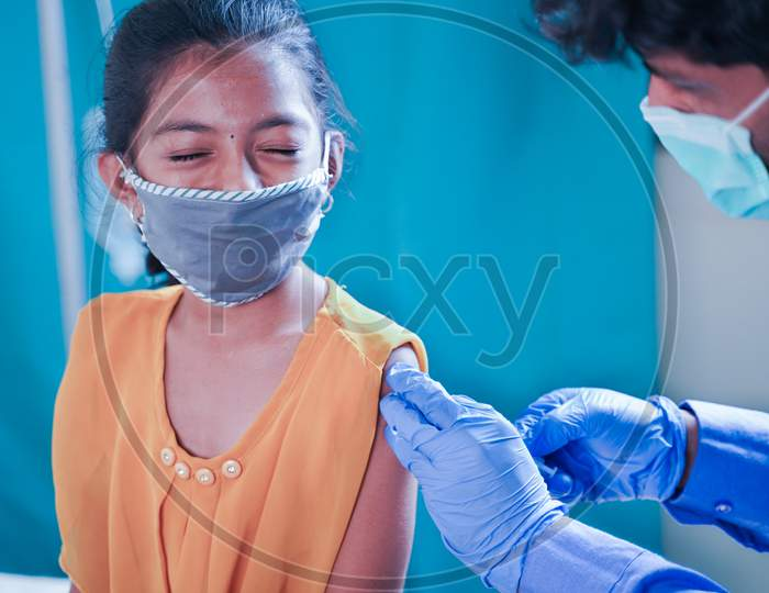 Concept Of Covid-19 Coronavirus Vaccination For Children - Young Girl Kid Getting Jab Or Vaccinated To Against Covid At Hospital