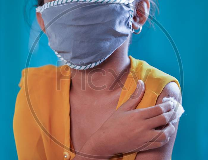 Portrait Of Covid Vaccinated Young Gril Kid With Medical Mask Looking Camera By Holding Arm - Concept Of Coronavirus Vaccination Trials For Children