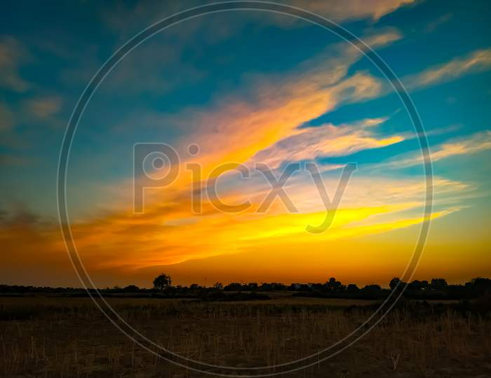 Field Under The Gorgeous Yellow And Blue Sunset Sky