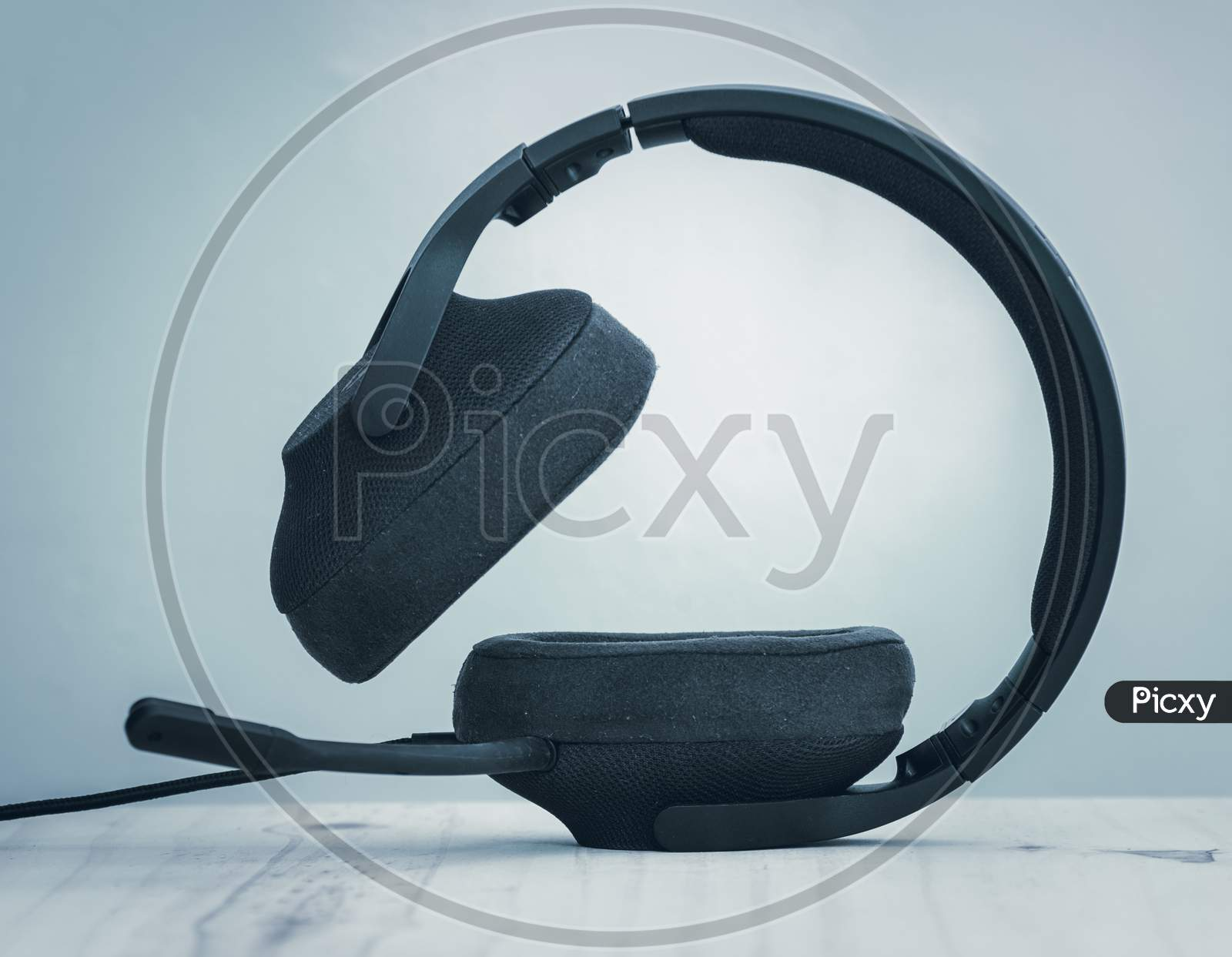 Black Gaming Headset With Detachable Cables, Microphone, And Adjustable Headband, The Concept Of Modern Technology, Headset Standing On An Ear Cup Side View.