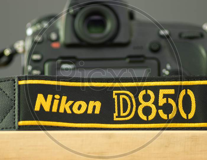 Galle, Sri Lanka - 02 17 2021: Nikon D850 Dslr And Camera Strap On Wooden Table Close Up, Brand New Nikon Logo Embroidered In Yellow Into A Black Ribbon, Professional Factory Finishing Product.