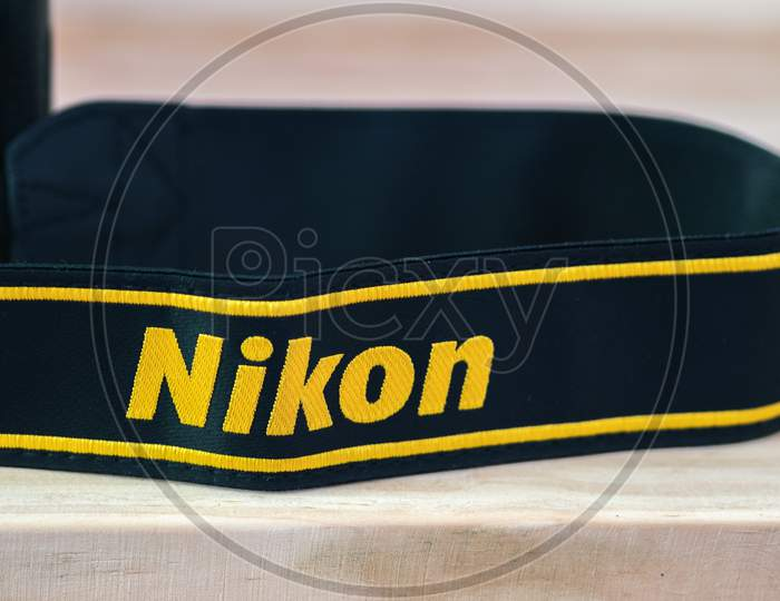 Galle, Sri Lanka - 02 17 2021: Nikon Dslr Camera Strap On Wooden Table Close Up, Brand New Nikon Logo Embroidered In Yellow Into A Black Ribbon, Professional-Grade Factory Finishing Product.