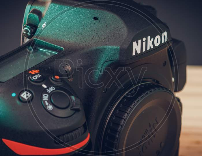 Galle, Sri Lanka - 02 17 2021: Nikon D850 Dslr Body With Camera Body Cap, Top Lcd Display, And Front Dials And On Off Switch Close Up. Modern Professional Camera Body On A Wooden Table View From Top.