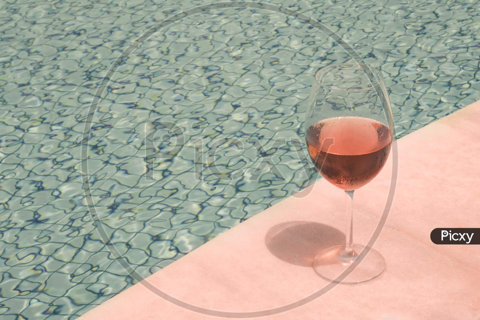 Crystal Goblet With Rose Wine On The Edge Of A Swimming Pool. High Class People Drink Concept.