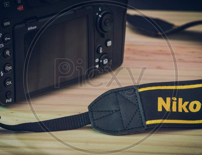 Sri Lanka - 02 17 2021: Modern Professional Level Dslr Body And Neck Trap With Nikon Brand Name Embraided On A Wooden Table, Nikon D850 Close Up Photograph.