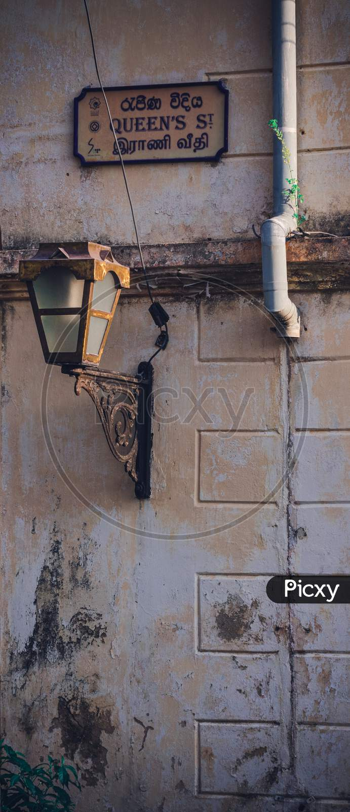 Steel Street Lamp And Queen'S Street Sign In A Rusty Wall Galle Fort. Evening Light Brighten Up The Side Of The Lamp .