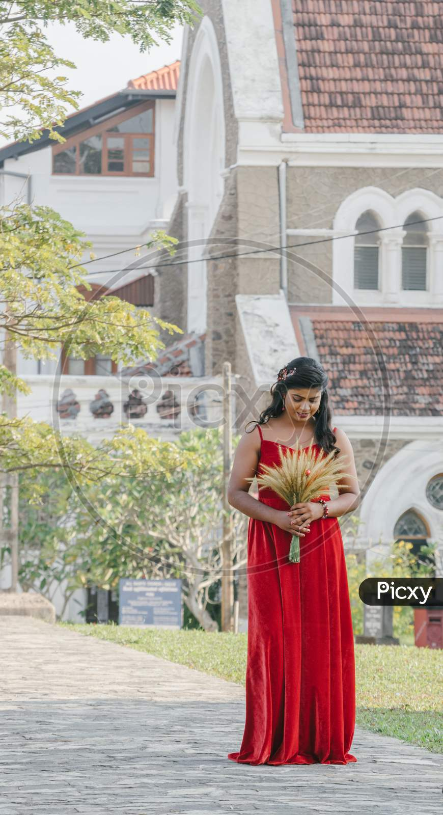 Galle, Sri Lanka - 02 12 2021: Young Beautiful Model In Long Red Dress Posing For A Photoshoot In The Streets Of Galle Fort In Front Of Famous All Saint'S Church In The Background.
