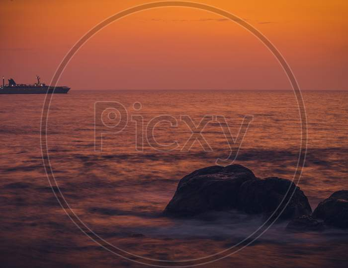 Colorful Sunset View From Galle Dutch Fort Evening, Sailboat In The Horizon, After Sundown Bright Orange And Yellow Skies, Long Exposure Photograph.