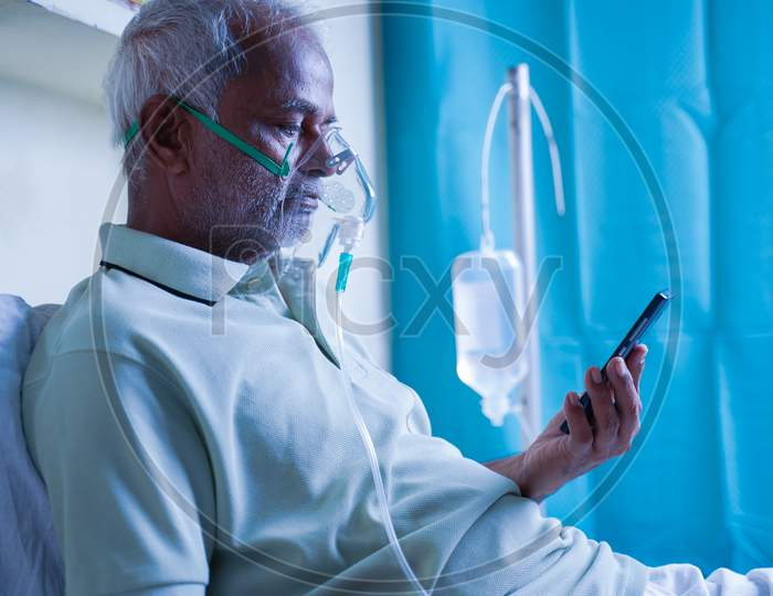 Sick Elderly Man With On Ventilator Oxygen Mask Checking Health Status Report On Mobile Phone - Concept Of Shortness On Breath Or Lung Infection Treatment For Covid-19 Coronavirus Infection
