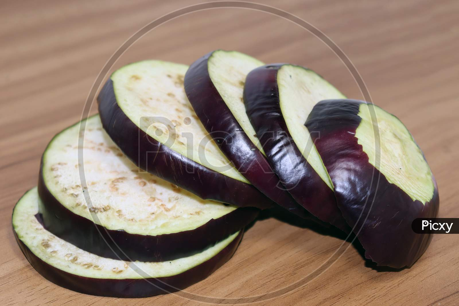Violet Colored Brinjal On Wooden Table For Cooking