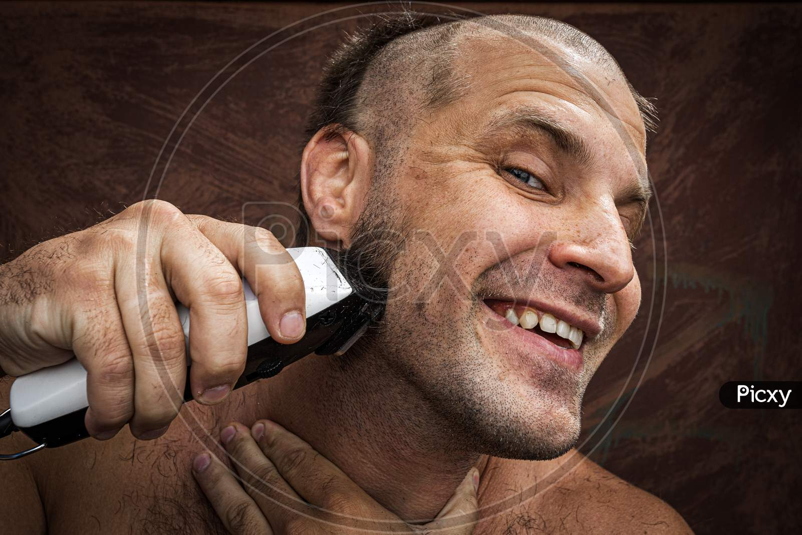 Close-Up Portrait Of Handsome Shirtless Man Shaving His Beard With An Electric Razor And Gritting His Teeth, Against Brutal Background. Concept Of Male Home Care Without Beauty Salons