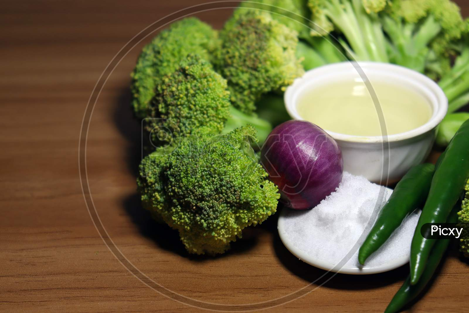 Sliced Broccoli With Spices Stock On Wooden Table