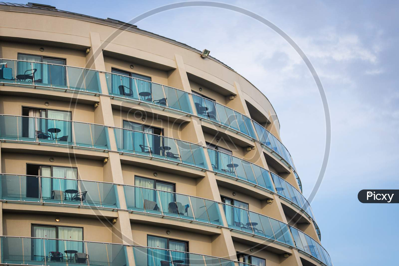 A Residential Building With Flat, Identical Balconies With Ripped Air Conditioners And  Glass. Balcony Pattern