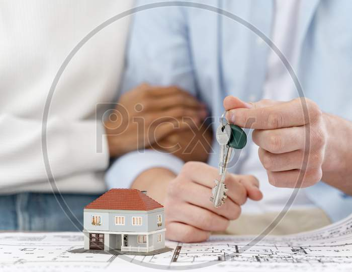 embraced defocused couple holding keys their new house