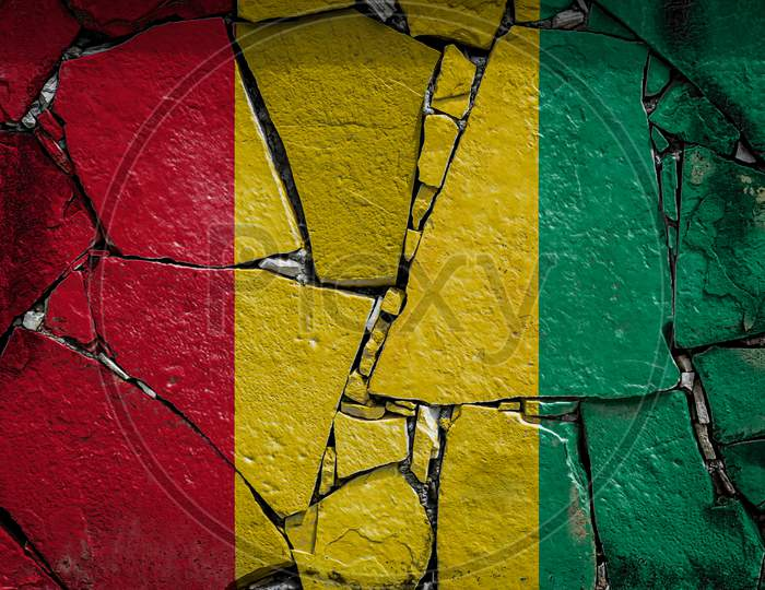 National Flag Of Guinea  Depicting In Paint Colors On An Old Stone Wall. Flag  Banner On Broken  Wall Background.