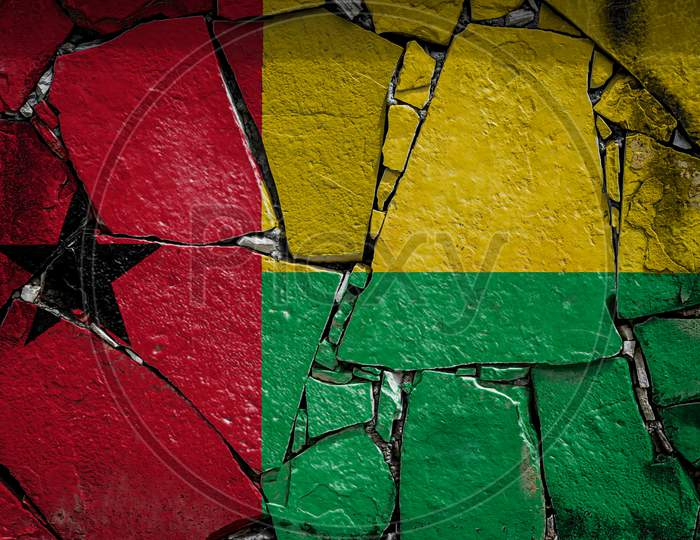 National Flag Of  Guinea Bissau Depicting In Paint Colors On An Old Stone Wall. Flag  Banner On Broken  Wall Background.