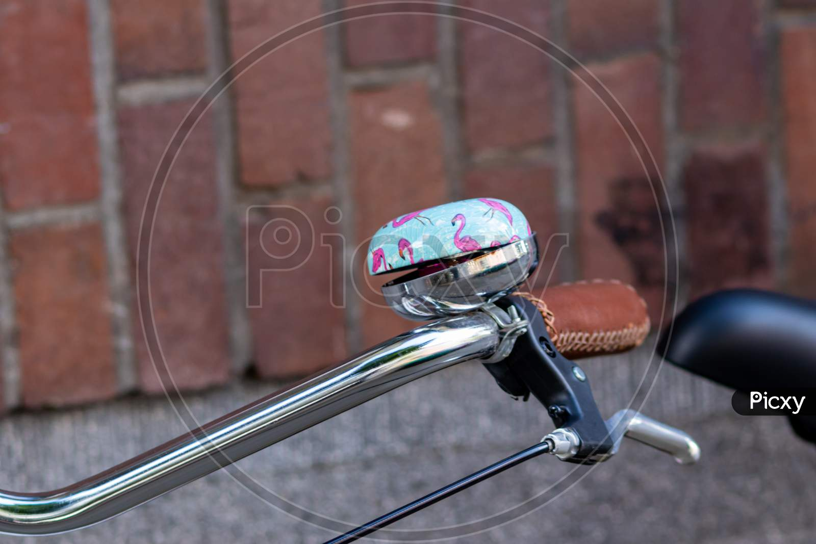 Beautiful bike bell with a shiny finish at a silver metal bicycle handlebar as sustainable mobility and a lot of copy space and a blurred background shows safety aspects and emission free transportation