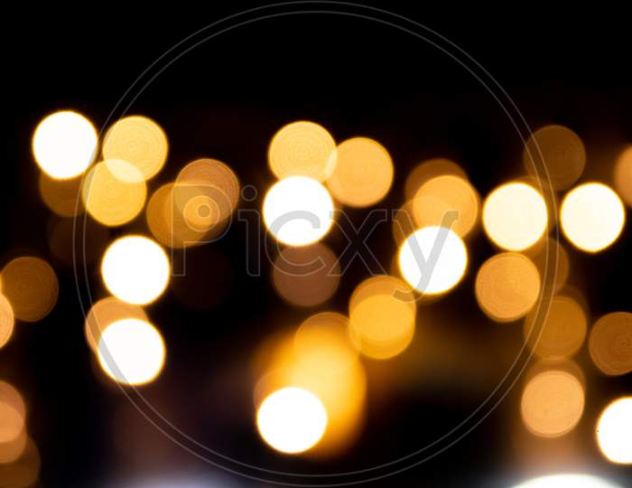 Shiny golden bokeh background for festive celebrations like christmas, silvester and a happy new year party as well as elegant invitation cards to celebrate with glitter rain and noble guests together