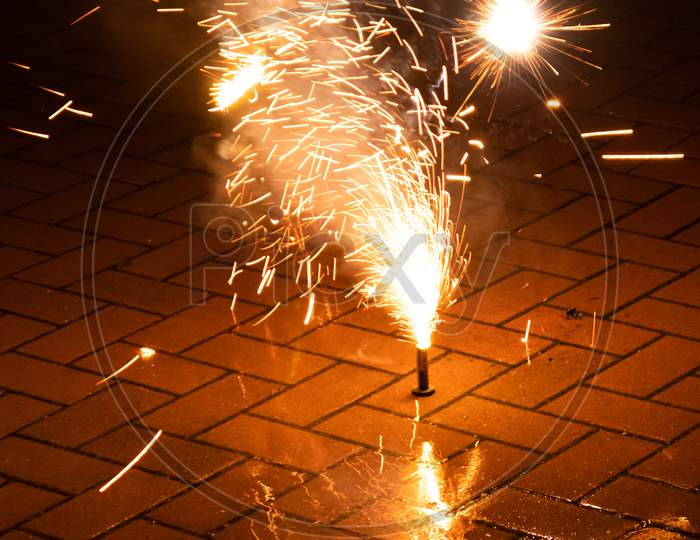Colorful fireworks illuminates the silvester night with firecrackers, bangers and explosive pyrotechnics and fountains of light to celebrate into a happy new year on a silvester party with friends