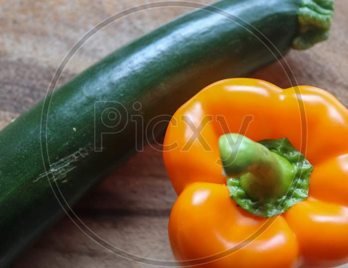 Selective Focus. Colorful Single Orange Pepper On A Wooden Surface In A Kitchen.