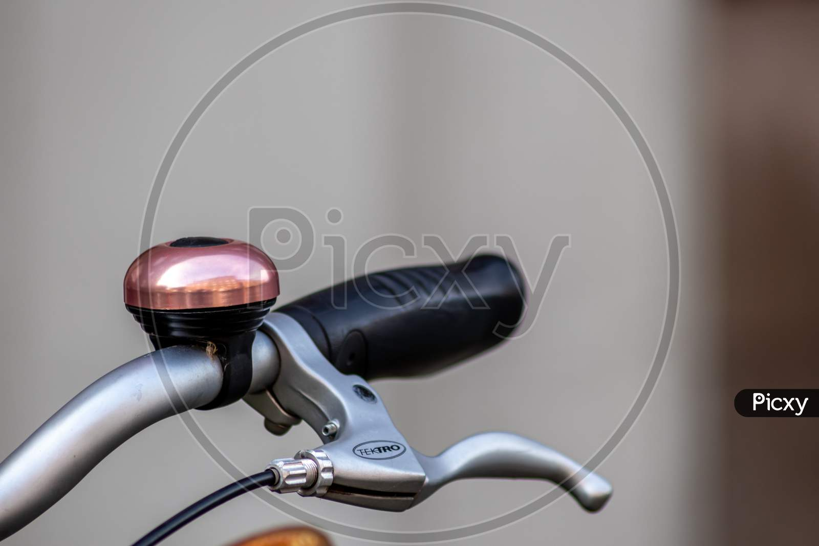 Beautiful bike bell with a shiny finish at a silver metal bicycle handlebar with a black grip and a lot of copy space and a blurred background shows safety aspects and emission free transportation