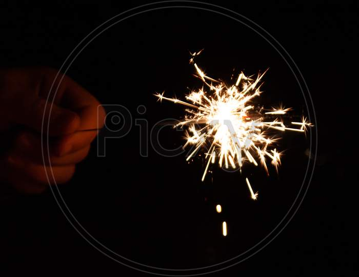 beautiful sparkler hold in the hand of a child during happy new year wishing on new years eve in the dark night with silver sparkles and a fiery glow in the night