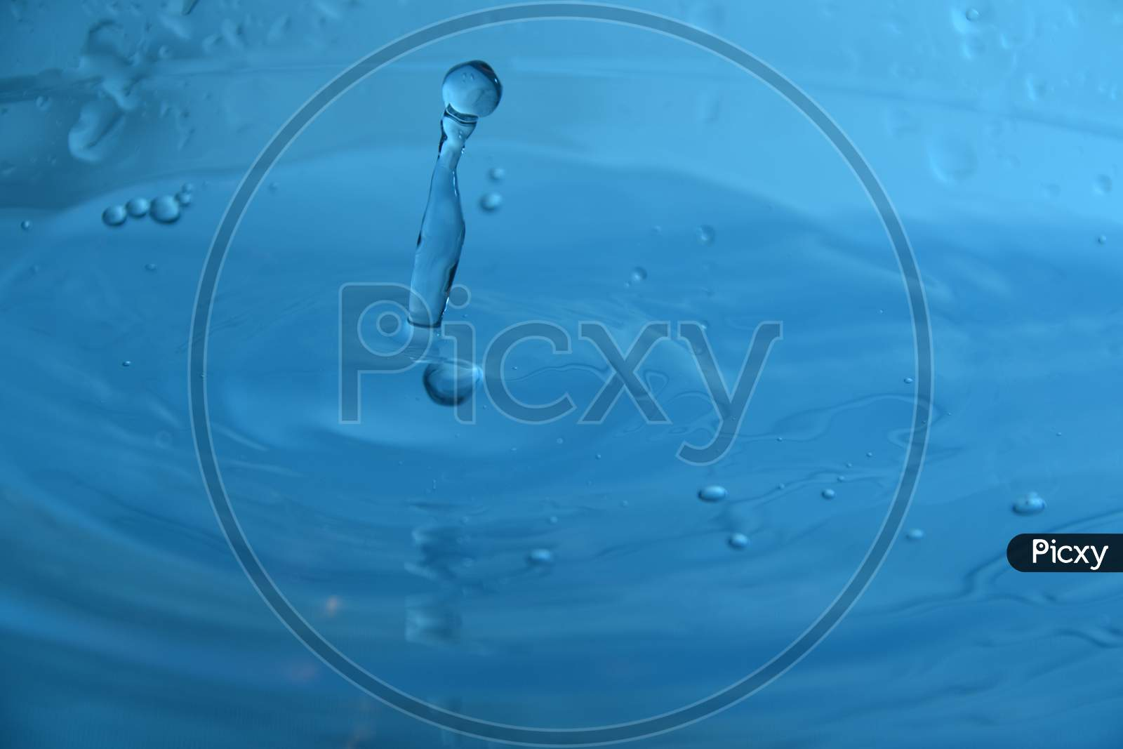 Splash With Drop Of Water With Blue Background