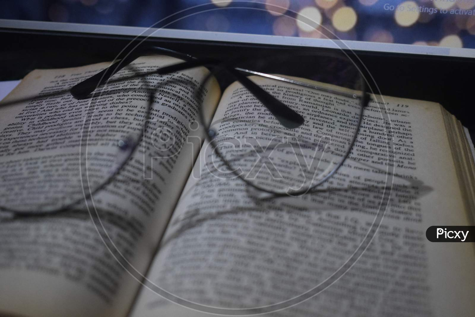 Glasses on book with laptop in background