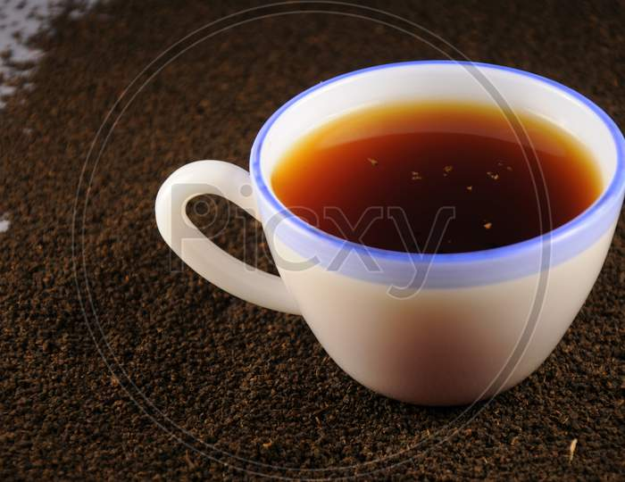 Cup Of Tea With And Black Tea Leaves